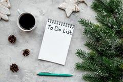 Новый Год планирования Тетрадь с для того чтобы сделать список около игрушек рождества, елевой ветви и pinecones на серой каменно Стоковая Фотография