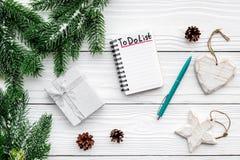 Новый Год планирования Тетрадь с для того чтобы сделать список около игрушек рождества, елевой ветви и pinecones на белой деревян Стоковое Фото