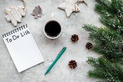 Новый Год планирования Тетрадь с для того чтобы сделать список около игрушек рождества, елевой ветви и pinecones на серой каменно Стоковые Фото