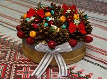 Новый Год, праздничный натюрморт с гайками ягод конусов на таблице стоковое изображение