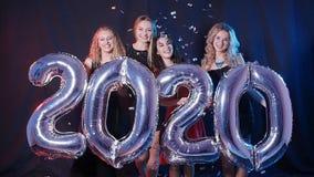 Новый Год принципиальной схемы счастливое Группа в составе молодые женщины имеет потеху и держит более большие 2020 акции видеоматериалы