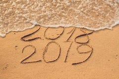 Новый Год 2019 приходя концепция - надпись 2018 и 2019 на песке пляжа, волна почти покрывает числа 2018 стоковые изображения rf