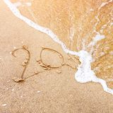 Новый Год приходя концепция - надпись 20 на песке пляжа, волне моря покрывает числа 2017 или 2018 Новый Год Стоковое фото RF