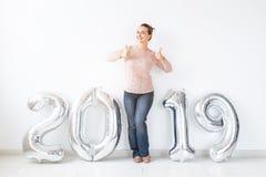 Новый 2019 год приходя концепция - счастливая женщина показывая большие пальцы руки вверх около серебряных покрашенных номеров вн стоковая фотография