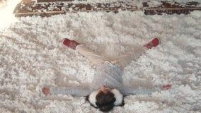 Новый Год рождества ребенок делает ангела лежа на снеге маленькая девочка околпачивает вокруг и лежит в искусственном снеге сток-видео