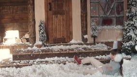 Новый Год рождества ребенок околпачивает вокруг и лежит в искусственном снеге портрет ребенка в украшениях рождества сток-видео