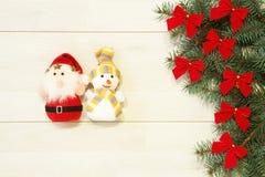 Новый Год/рождественская елка с смычками красного цвета, Санта и снеговик забавляются на деревянном шаблоне предпосылки Стоковое Изображение