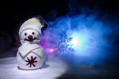 Новый Год Снеговик разгржает подарки на Новый Год Белый снеговик окруженный рождественскими елками на предпосылке вечера Оформлен Стоковые Изображения