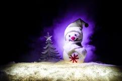 Новый Год Снеговик разгржает подарки на Новый Год Белый снеговик окруженный рождественскими елками на предпосылке вечера Оформлен Стоковое фото RF