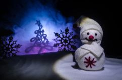Новый Год Снеговик разгржает подарки на Новый Год Белый снеговик окруженный рождественскими елками на предпосылке вечера Оформлен Стоковое Изображение RF