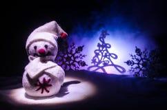 Новый Год Снеговик разгржает подарки на Новый Год Белый снеговик окруженный рождественскими елками на предпосылке вечера Оформлен Стоковая Фотография