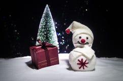 Новый Год Снеговик разгржает подарки на Новый Год Белый снеговик окруженный рождественскими елками на предпосылке вечера Оформлен Стоковое Фото