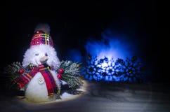 Новый Год Снеговик разгржает подарки на Новый Год Белый снеговик окруженный рождественскими елками на предпосылке вечера Оформлен Стоковые Фотографии RF