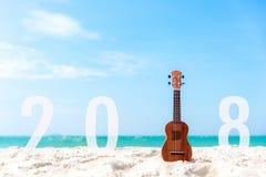 Новый Год 2018 с гавайской гитарой гитары для ослабляет на красивого предпосылке пляжа и голубого неба на сезон и праздник стоковое изображение