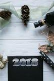 Новый Год и зима установленные на белую деревянную предпосылку с деталями черных и естественных и золота, striped золотым и белым Стоковые Фото