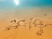 Новый Год 2014 концепци-написанный в песке на пляже Стоковые Изображения