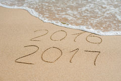Новый Год 2017 приходя концепция - надпись 2016 и 2017 на песке пляжа, волна почти покрывает числа 2016 Стоковая Фотография RF
