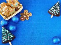 Новый Год сини предпосылки Украшения рождества, люди пряника и мед-торты обрамляют Стоковая Фотография RF