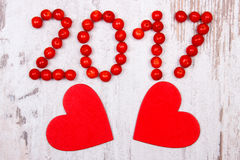 Новый Год 2017 сделал красной калины и красных деревянных сердец на старой деревянной предпосылке Стоковое Изображение RF
