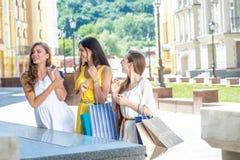 Новый магазин выхода Девушки держа хозяйственные сумки и стоят выходы Стоковые Фотографии RF