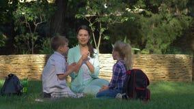 Новый метод образования, счастливый мальчик ученого и девушка с женщиной учителя прочитали книги и обнимать во время урока видеоматериал