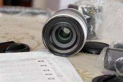 Новый объектив фотоаппарата с крышками и инструкция на таблице стоковое изображение