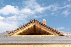 Новый дом рамки под конструкцией Крыша с гонт асфальта, печной трубой и материалом изоляции стоковое фото