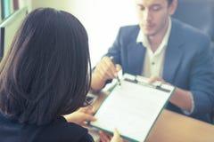 Новый работодатель был приглашен подписать контракт работы после собеседования для приема на работу стоковые изображения rf