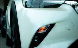 Новый роскошный белый автомобиль припаркованный в современном выставочном зале Офис автосалона Технология электрического или гибр стоковое фото rf