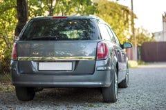 Новый сияющий серый автомобиль припаркованный на дороге пригородов гравия на запачканной солнечной предпосылке лета стоковое фото rf