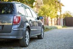 Новый сияющий серый автомобиль припаркованный на дороге пригородов гравия на запачканной солнечной предпосылке лета стоковая фотография