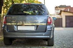 Новый сияющий серый автомобиль припаркованный на дороге пригородов гравия на запачканной солнечной предпосылке лета стоковые фотографии rf