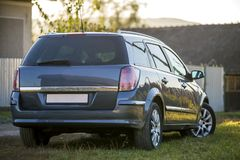 Новый сияющий серый автомобиль припаркованный на зеленой траве на запачканной предпосылке солнечного лета сельской стоковая фотография rf