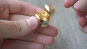 Новый спутник непоседы золота, закручивая в руку молодого человека на серой предпосылке видеоматериал