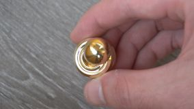 Новый спутник непоседы золота, закручивая в руку молодого человека на серой предпосылке сток-видео