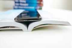 Новый smartphone корабля- флагмана Яблока Iphone x помещенный на книге перемещения стоковое изображение rf