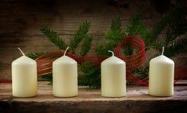 4 новых белых свечи с елевыми хворостинами и красным ждать ленты Стоковое фото RF
