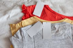 3 новых ребенк или футболка женщин, серые, красные, желтые цвета, с чистым ярлыком на белой предпосылке o стоковое фото