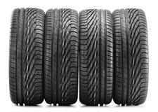 4 новых черных автошины на белизне Стоковые Фотографии RF