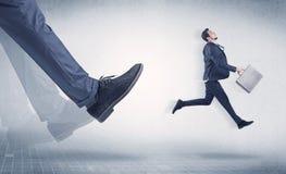 Нога бизнесмена пиная малый предпринимателя Стоковое Изображение