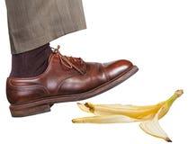 Нога в правом коричневом ботинке смещает на корку банана Стоковые Изображения
