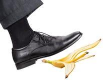 Нога в правом черном ботинке смещает на корку банана Стоковая Фотография RF