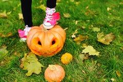 Нога в розовых ботинках стоит на тыкве с высекаенными глазами на хеллоуине стоковое фото rf