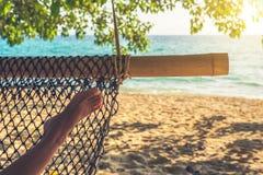 Нога женщины в гамаке на красивом пляже острова Концепция релаксации праздников Стоковые Фото