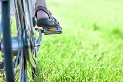 Нога женщины на педали велосипеда на крупном плане зеленой травы Стоковые Фото