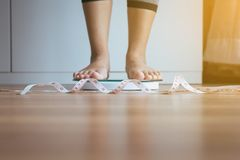 Нога женщины стоя дальше весит масштабы с рулеткой в переднем плане, потерей веса стоковая фотография rf