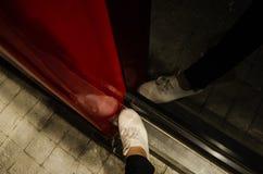 Нога женщины с белыми ботинками смотрит сверху с отражением себя в черном зеркале с красной структурой стоковые фотографии rf