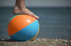Нога и шарик на пляже Стоковое Изображение
