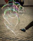 Нога молодого мальчика пиная большие пузыри мыла стоковые изображения rf