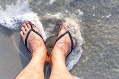 Нога мужчины с темповыми сальто сальто носки пока стоящ на пляже стоковая фотография